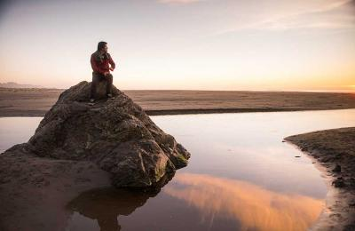 Enjoying the sunset from a rock in the little river at Moonstone Beach