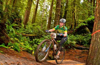 Member of the HSU Cycling Club racing to victory during local race in Arcata Community Forest